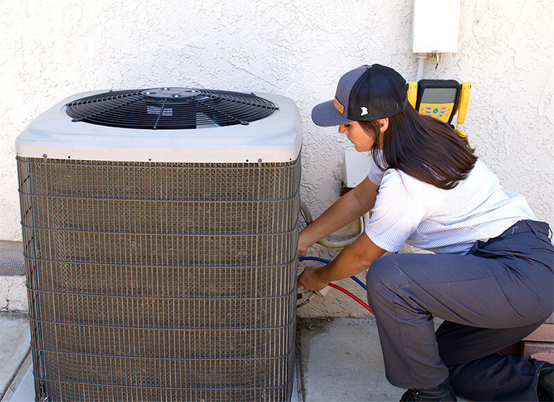 HVAC Technician performing maintenance on an outdoor AC unit at a home