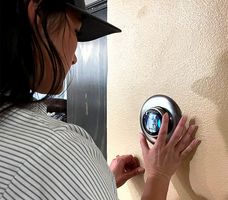HVAC Technician Installing a Smart Thermostat in a Home